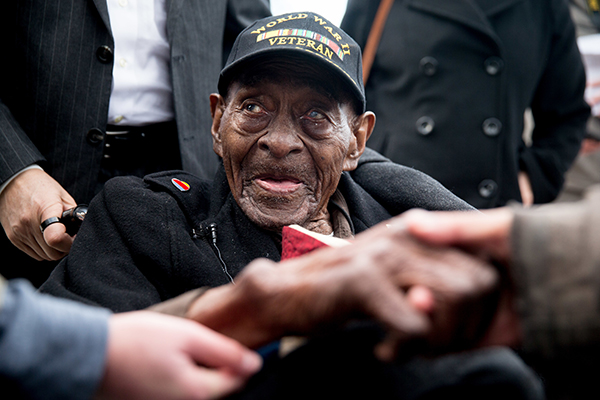 Frank Levingston Jr., of Lake Charles, La., who at 110 is believed to be America's oldest military veteran, is greeted by visitors following a wreath laying ceremony to mark the anniversary of Pearl Harbor at the World War II Memorial, Monday, Dec. 7, 2015, in Washington. The surprise attack on Pearl Harbor in 1941 by the Japanese killed 2,403 Americans and was the catalyst for the United States to become involved in World War II. (AP Photo/Andrew Harnik)