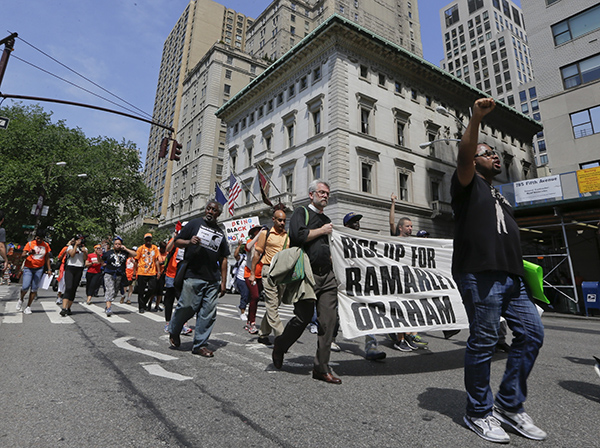 Protestors march down fifth avenue in support of the family of Ramarley Graham Thursday, June 2, 2016, in New York. The mother of the unarmed black teenager fatally shot by a white policeman in front of his grandmother and 6-year-old brother joined supporters Thursday for a 17-mile march to police headquarters to demand that the officers involved in the 2012 slaying be fired. (AP Photo/Frank Franklin II)