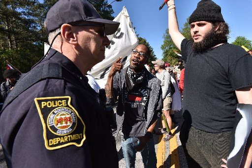 April 23, 2016 Stone Mountain - A counter-protester yells at police as they try to get past police and to a white power protest at Stone Mountain Park on Saturday, April 23, 2016. Violent protests surrounding a white power rally at Stone Mountain have caused officials to shut down public attractions at the park. (HYOSUB SHIN)