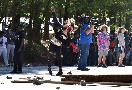 April 23, 2016 Stone Mountain - A counter-protester throws a rock at police during a clash at Stone Mountain Park on Saturday, April 23, 2016. Violent protests surrounding a white power rally at Stone Mountain have caused officials to shut down public attractions at the park. (HYOSUB SHIN)