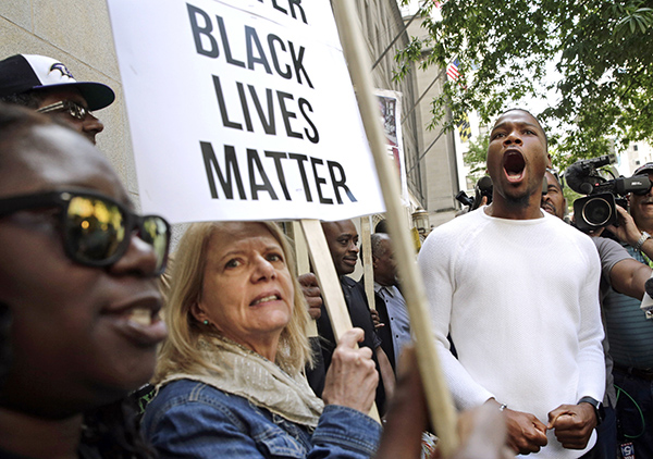 FILE- In this May 23, 2016, file photo, protesters gather outside of a courthouse after Officer Edward Nero, one of six Baltimore city police officers charged in connection to the death of Freddie Gray, was acquitted of all charges in his trial in Baltimore. Black activists in Baltimore and beyond say they are disappointed but not discouraged after neither of the first two police officers to stand trial in the death of Gray was convicted. (AP Photo/Patrick Semansky, File)