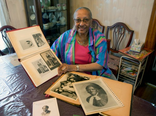 In this Thursday, May 19, 2016 photo, Judith Bryant, a great-great-grandniece of Harriet Tubman, poses with photos of Tubman and other family members at her home in Auburn, N.Y. Bryant's great-great grandfather was Tubman's brother, and was among the dozens of slaves she guided north to freedom. Tubman had been free for a decade in 1859, when she bought a parcel of land on the outskirts of Auburn, about 25 miles west of Syracuse. (AP Photo/Mike Groll)