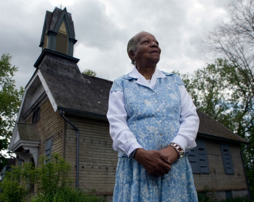 In this Thursday, May 19, 2016 photo, Pauline Copes Johnson, a great-great-grandniece of Harriet Tubman, poses outside the Thompson A.M.E. Zion Church in Auburn, N.Y. The Harriet Tubman National Historical Park would encompass that 31-acre site plus the A.M.E. Zion Church about a mile away where Tubman worshipped. The weathered clapboard church is boarded up now and offers sanctuary only for neighborhood birds. (AP Photo/Mike Groll)