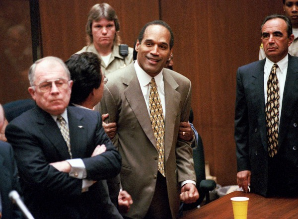 In this Oct. 3, 1995 file photo, O.J. Simpson, center, clenches his fists in victory after the jury said he was not guilty in the murders of his ex-wife Nicole Brown Simpson and her friend Ronald Goldman in a Los Angeles courtroom as attorneys F. Lee Bailey, left, and Robert Shapiro, right, look on. (AP Photo/Los Angeles Daily News, Myung Chun, Pool)