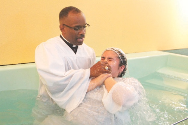Pastor Smith baptizes one of nine new members. (photo by Troy Tieuel)