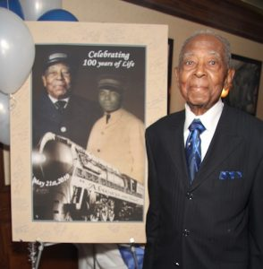 Lee Wesley Gibson at his 100th birthday party in 2010, standing by poster of him as a young Pullman Porter.