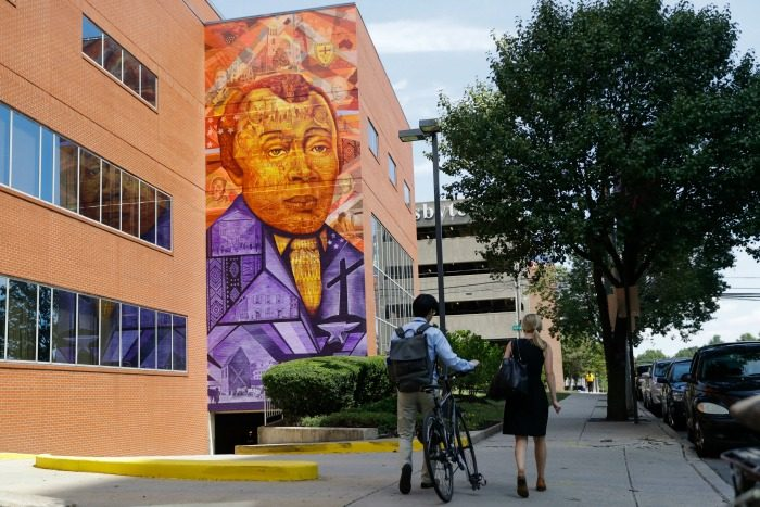 People walk past a Philadelphia Mural Arts Program piece depicting Bishop Richard Allen and the African Methodist Episcopal Church, in Philadelphia, Wednesday, July 6, 2016. The church marks its 200th anniversary in the city where it was founded by a former slave. (AP Photo/Matt Rourke)