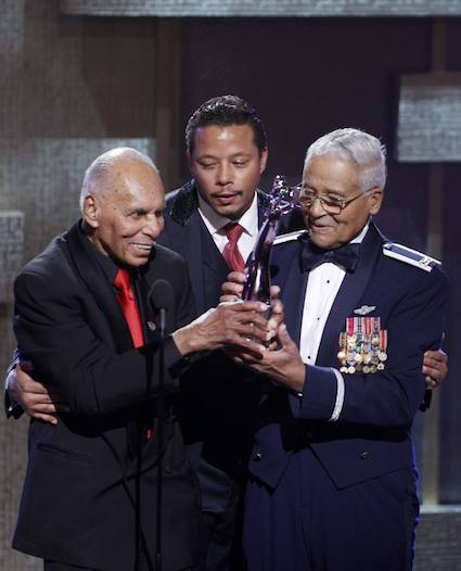 BET honorees Tuskegee Airmen Colonel Charles McGee USAF Ret. and Dr. Roscoe C. Brown Jr. hold their BET Honor for Service, as actor Terrence Howard hugs them during the BET Honors at the Warner Theatre in Washington on Saturday, Jan. 14, 2012. (AP Photo/Jose Luis Magana)