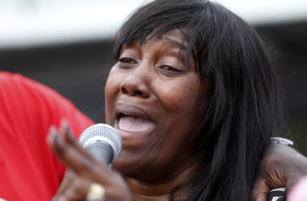 Sandra Sterling, aunt of Alton Sterling, who was shot and killed during a scuffle with police officers, speaks at a vigil outside the Triple S convenience store in Baton Rouge, La., Wednesday, July 6, 2016. In a swift move by authorities to keep tensions from boiling over, the U.S. Justice Department launched a civil rights investigation Wednesday into the video-recorded killing of Sterling, who was shot as he scuffled with two white police officers on the pavement outside the convenience store. (AP Photo/Gerald Herbert)