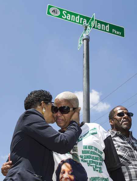 Geneva Reed-Veal, left, mother of Sandra Bland, embraces her daughter, Shante Needham during a ceremony renaming University Boulevard to Sandra Bland Parkway, Friday, April 15, 2016, in Prairie View, Texas. The street was renamed near the location where Bland, who died in custody at the Waller County Jail, was arrested. (Brett Coomer/Houston Chronicle via AP)