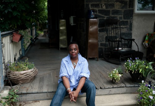 "In this July 1, 2016 photo, artist Vashti Dubois poses on the porch of The Colored Girls Museum in the Germantown section of Philadelphia. Dubois has turned her 127-year-old house into a sanctuary for and monument to what its founder calls ""everyday black girls."" The museum is a sensory experience taking visitors on a journey of loss, joy, healing and memory. Each room is curated by different artists, whose work and objects live alongside Dubois' family's belongings. (AP Photo/Jacqueline Larma)"