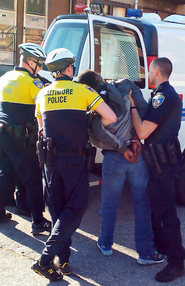 Freddie Gray being taken away by police officers on the day of his controversial death.