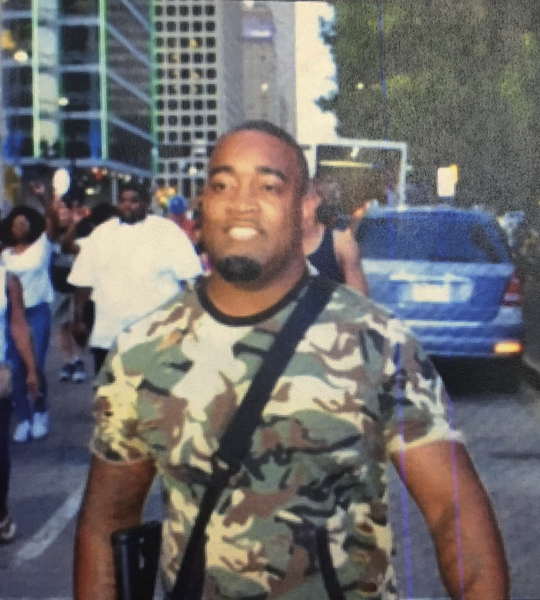 "A photo provided by Dallas police shows open-carry activist Mark Hughes at a rally against excessive use of force by police, Thursday, July 7, 2016, in Dallas. Hughes told a television station that he was ""defamed"" by the Dallas Police Department, which tweeted the photo of him and described him as a suspect in the shootings of police officers. Hughes turned himself in to police, and was released a short time later. Another man, Micah Johnson, was later identified as the shooter who killed five officers. Johnson was killed in a confrontation with police. (Dallas police via AP)"