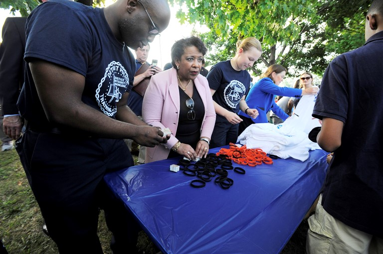 Attorney General Loretta Lynch hands out wristbands, Tuesday Aug. 2, 2016, during a National Night Out event at Fitzpatrick Play Field in Detroit. (Steve Perez/Detroit News via AP)