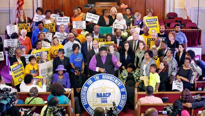 North Carolina NAACP president, Rev. William Barber, center at podium, gestures as he is surrounded by supporters during a news conference at the Third Street Bethel AME Church in Richmond, Va., Tuesday, June 21, 2016. The press conference was held to talk about the appeal before the 4th U.S. Circuit Court of Appeals on North Carolina's major rewrite of voting laws in 2013. (AP Photo/Steve Helber)