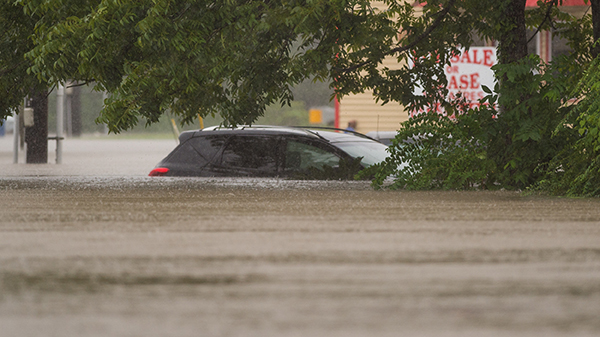 A car sits submerged in a flooded residential neighborhood in Carencro, La., Saturday, Aug. 13, 2016, as record rainfall causes flooding across south Louisiana. (Scott Clause/The Lafayette Advertiser via AP)