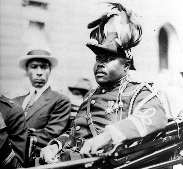 """FILE - In this August 1922 file photo, Marcus Garvey is shown in a military uniform as the """"Provisional President of Africa"""" during a parade on the opening day of the annual Convention of the Negro Peoples of the World along Lenox Avenue in Harlem borough of New York. The son ofMarcus Garvey on Aug. 17, 2016, said his father's 129th birthday marked the perfect day to begin a public push for a presidential pardon to exonerate Garvey for an unjust conviction. Dr. Julius W. Garvey wants President Barack Obama to clear his father's name from a mail fraud conviction that caused Marcus Garvey to be deported from the United States to his native Jamaica. (AP Photo/File)"""