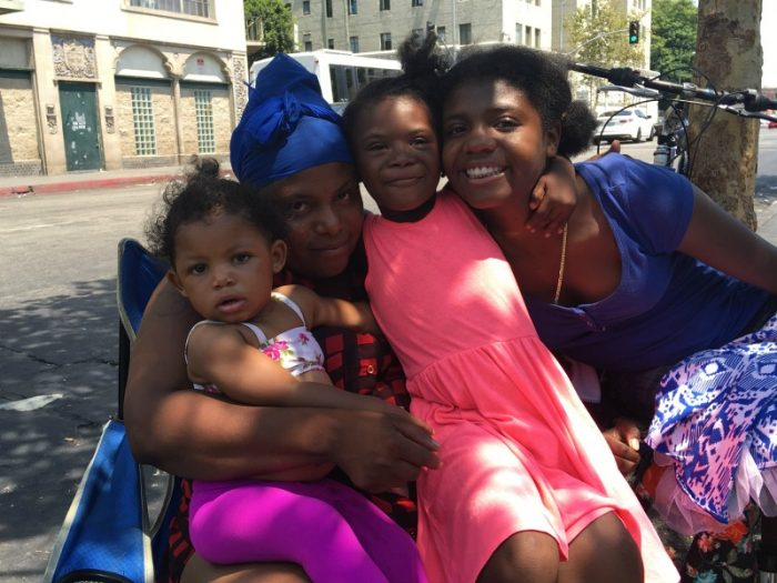 Andria Patterson and her children, 1-year-old Skylar, 6-year-old Nevaeh, and 15-year-old Sierra enjoy a moment of cool under a tree in front of Downtown L.A.'s Skid Row's Midnight Mission. (LAS photo/ Charlene Muhammad)