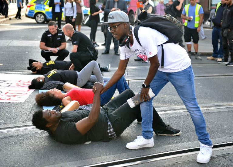 A man shakes hands with one of the activists as they lay on the road outside Nottingham Theatre Royal during an attempt to shut down part of the city centre tram and bus network in Nottingham, England Friday Aug. 5, 2016 to protest for social justice movement Black Lives Matter. Activists affiliated with the U.S.-based group Black Lives Matter have blocked a road leading to Heathrow Airport, and Nottinghamand city centre along with protests in other British cities (Edward Smith/PA via AP)