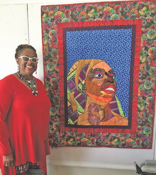 Rev. Judi Wortham-Sauls displays one of her quilts. (photo by Cora Jackson-Fossett)