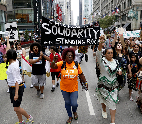 Protestors against the four-state Dakota Access pipeline march in downtown Friday, Sept. 9, 2016, in Chicago. Demonstrators say they're rallying in solidarity with Native Americans fighting to stop the pipeline that would run from North Dakota to Illinois. (AP Photo/Tae-Gyun Kim)