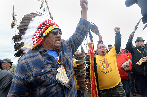 JR American Horse, left, raises his fist with others while leading a march to the Dakota Access Pipeline site in southern Morton County North Dakota. Several hundred protesters marched about a mile up Hwy 1806, Friday Sept. 9, 2016, from the protest camp to the area of the pipeline site where some archeological artifacts have been discovered. (Will Kincaid/The Bismarck Tribune via AP)