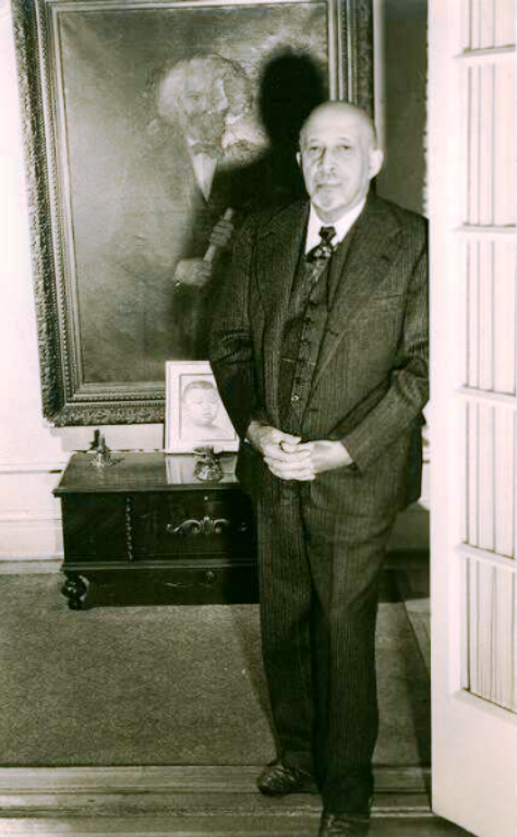 A photo of W.E.B. Du Bois at home around 1946, standing in front of a portrait of Frederick Douglass. (Photo: Department of Special Collections and University Archives, W.E.B. Du Bois Library, University of Massachusetts Amherst)