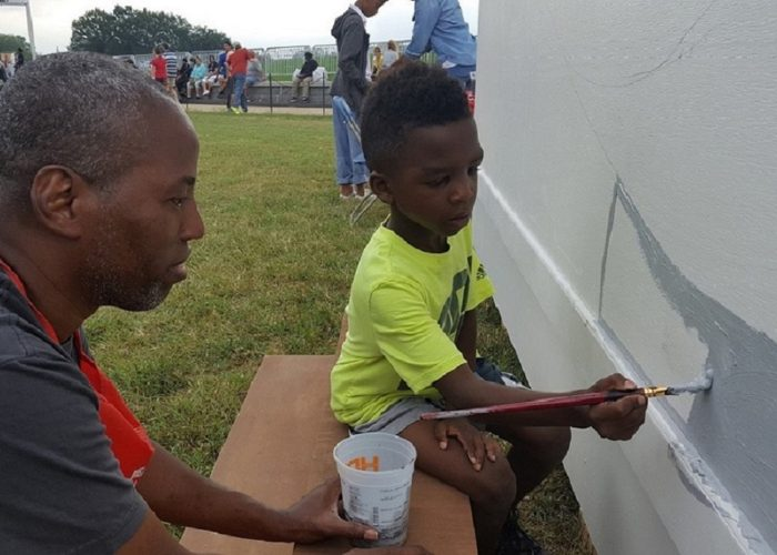 Cey Adams (left) watches Douglas Jackson, 7, stroke gray paint on a mural Sept. 24 during the grand opening celebration of the National Museum of African American History and Culture at the National Mall in Washington, D.C. (William J. Ford/The Washington Informer)