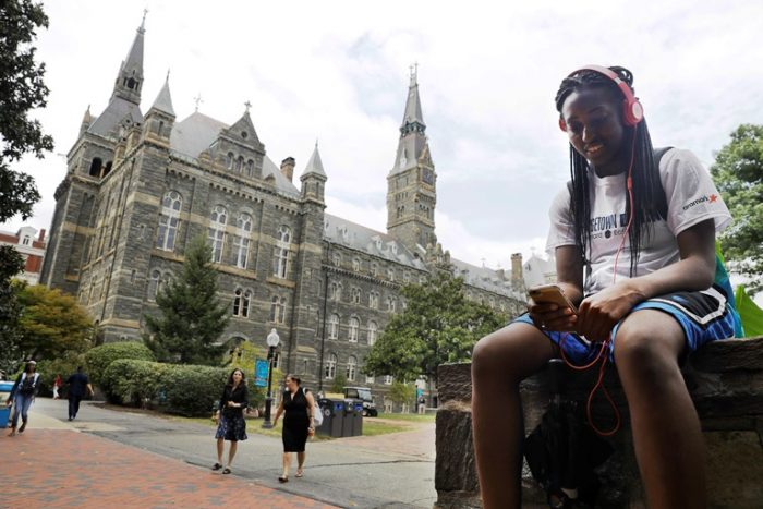 Deja Lindsey, 20, a junior at Georgetown University, talks on her cell phone in front of Healy Hall on campus, Thursday, Sept. 1, 2016, in Washington. (AP Photo/Jacquelyn Martin)