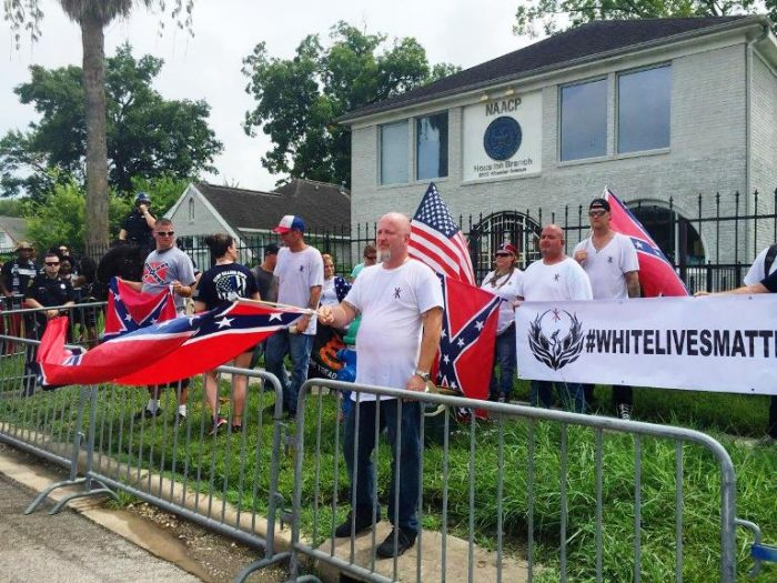 People with a White Lives Matter sign demonstrate in front of the NAACP office in Houston. (DARLA GUILLEN/AP)