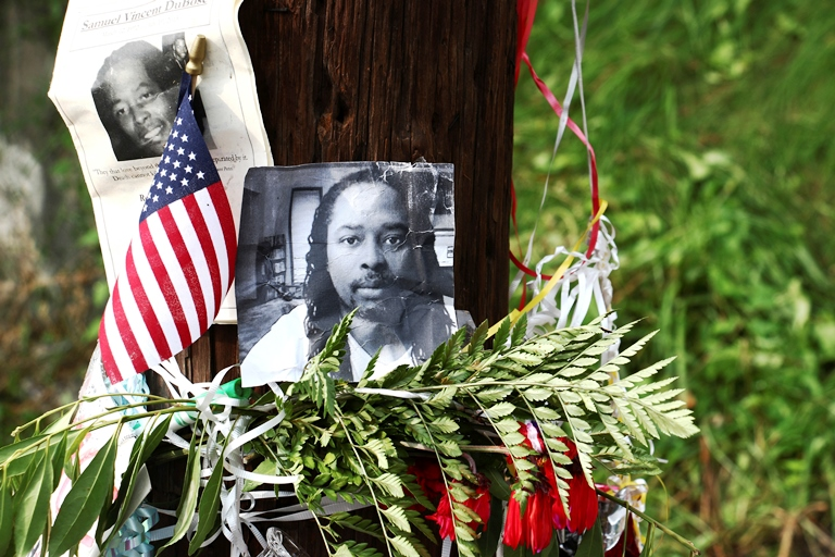 In this July 29, 2015, file photo, photos of Sam DuBose hang on a pole at a memorial near where he was shot and killed by a University of Cincinnati police officer during a July 19, 2015, traffic stop in Cincinnati. (AP Photo/Tom Uhlman, File)