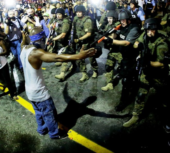 In this Aug. 9, 2014 file photo, police arrest a man as they disperse a protest in Ferguson, Mo. Police antagonized crowds gathered to protest the shooting of 18-year-old Michael Brown in Ferguson, violated free-speech rights and made it difficult to hold officers accountable, according to a U.S. Department of Justice report summary published Tuesday, June 30, 2015 by the St. Louis Post-Dispatch. (AP Photo/Charlie Riedel, File)