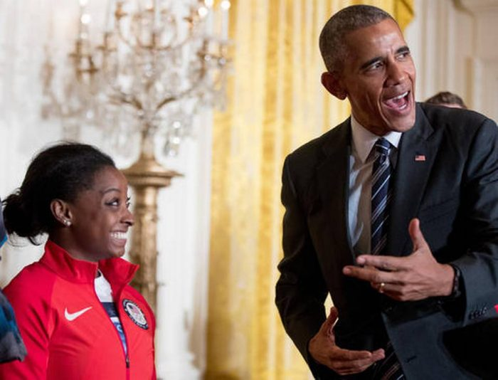 President Barack Obama leans over to speak to US Olympics gymnast Simone Biles in the East Room the White House in Washington, Thursday, Sept. 29, 2016, during a ceremony where he honored members of the 2016 United States Summer Olympic and Paralympic Teams. (Andrew Harnik/ AP Photo)