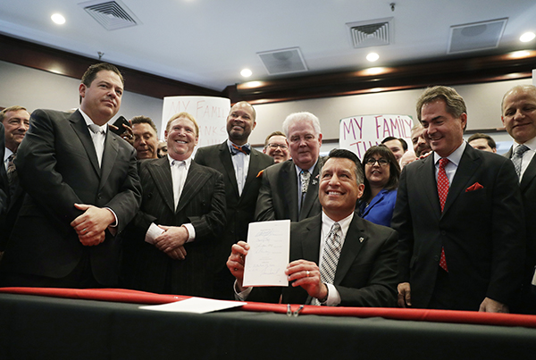 Nevada Governor Brian Sandoval holds up a bill he signed into law during a signing ceremony Monday, Oct. 17, 2016, in Las Vegas. Sandoval signed the bill into law that clears the way for a Las Vegas stadium that could be home to both UNLV football and the Raiders. (AP Photo/John Locher)
