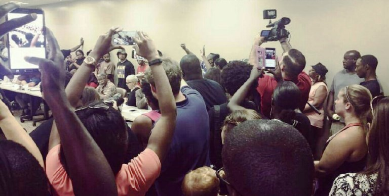 Protesters line the walls of a conference room at city hall during a police reform meeting in Baton Rouge, La. (The Drum)