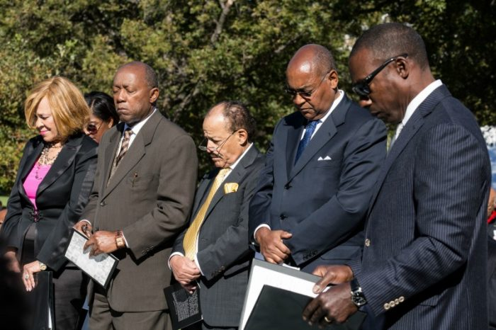 Members of the Texas Legislative Black Caucus, and the Texas African American History Memorial Foundation, bow their heads in prayer before the unveiling of the African American History Memorial outside the Texas State Capitol in Austin, Texas, on Saturday, Nov. 19, 2016. (Dave Creaney/Austin American-Statesman via AP)