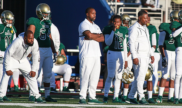 Hawkins head coach Mil'Von James (left) scrutinizes the game from the sidelines  (Photo by  Jevone Moore/Full Image 360)