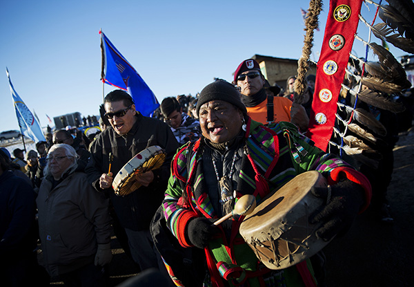 Dan Nanamkin, of the Colville Nez Perce Native American tribe in Nespelem, Wash., right, drums with a procession through the Oceti Sakowin camp after it was announced that the U.S. Army Corps of Engineers won't grant easement for the Dakota Access oil pipeline in Cannon Ball, N.D., Sunday, Dec. 4, 2016. (AP Photo/David Goldman)