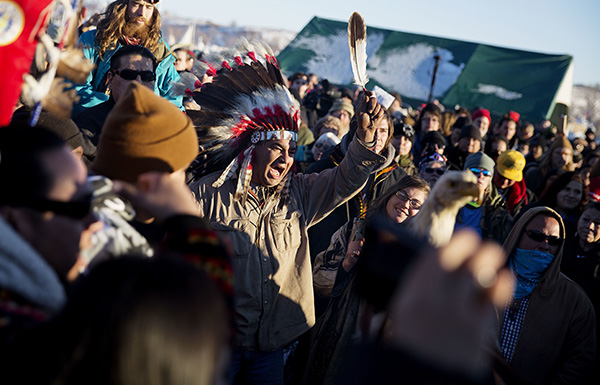 A crowd gathers in celebration at the Oceti Sakowin camp after it was announced that the U.S. Army Corps of Engineers won't grant easement for the Dakota Access oil pipeline in Cannon Ball, N.D., Sunday, Dec. 4, 2016. (AP Photo/David Goldman)
