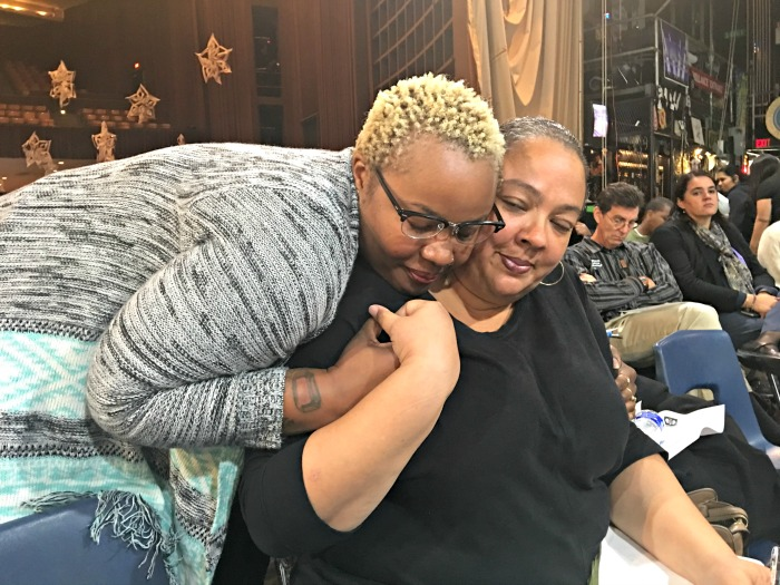 Community organizer Amber Rose Howard of A New Way of Life Reentry Project comforts organizer Dawn Modkins after her tearful testimony about the far-reaching impact police killings have on victims' families and their communities.