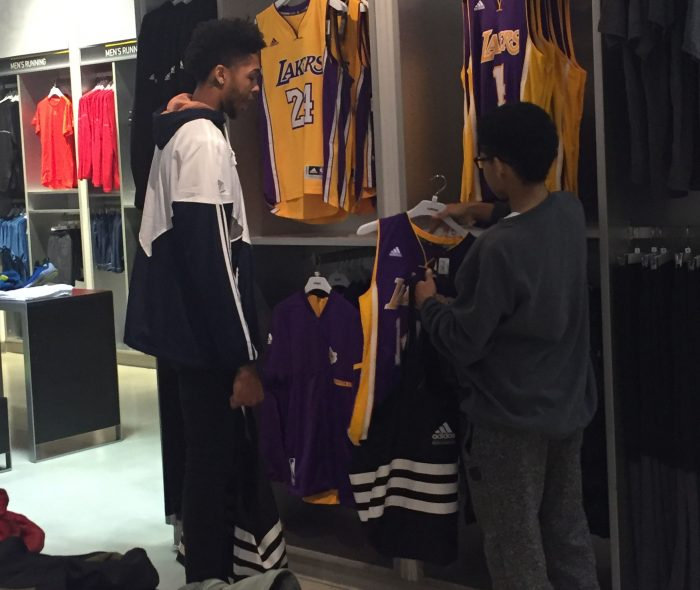 Ingram looks at Lakers jerseys with a shopping spree participant. (Courtesy of Excel Sports Management)