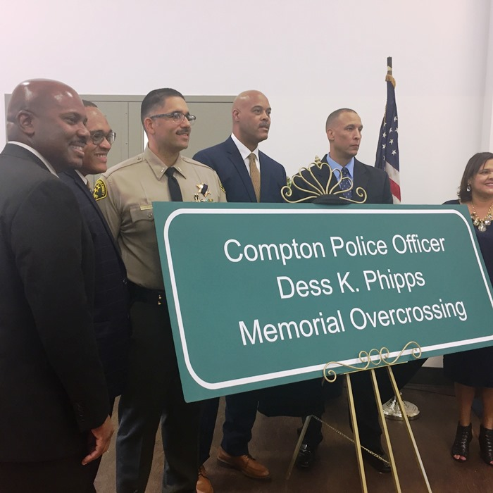 Asm. Mike A. Gipson with Compton Police Department and family members stand with Dedication Sign.