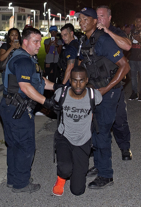 FILE - In this July 9, 2016, file photo, police officers arrest DeRay Mckesson for blocking Airline Highway during a protest in Baton Rouge, La. A Baton Rouge police officer who claims he was injured during the protest after a deadly police shooting filed a lawsuit Monday, Nov. 7, 2016, against prominent Black Lives Matter activist Mckesson. (AP Photo/Max Becherer, File)