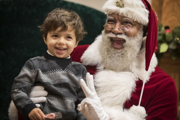 In this Thursday, Dec. 1, 2016 photo, Larry Jefferson, playing the role of Santa, gets a hug from Olivia Major, left, her sister Mallory and brother Preston, of Blaine, at the Santa Experience at Mall of America in Bloomington, Minn. The nation's largest mall is hosting its first-ever black Santa Claus. (Leila Navidi/Star Tribune via AP)