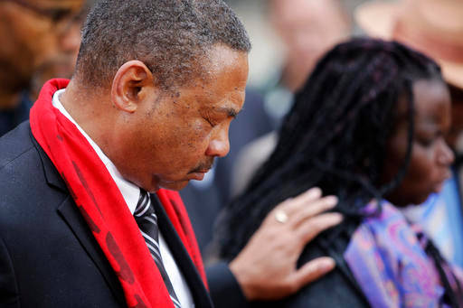Pastor Thomas Dixon, left, prays during a prayer vigil in front of the Charleston County Courthouse as the jury deliberates in the Michael Slager trial Monday, Dec. 5, 2016, in Charleston, S.C. (AP Photo/Mic Smith)