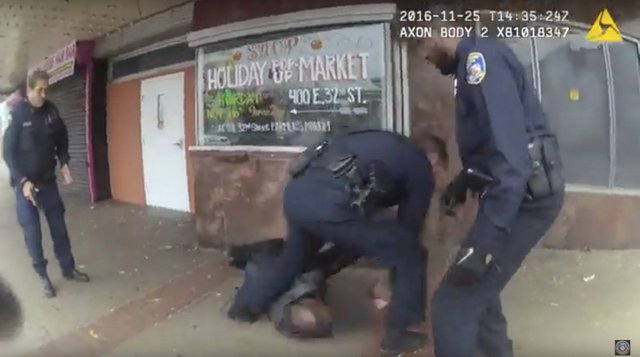 In this image taken from video from a body camera worn by a Baltimore police officer on Monday, Nov. 25, 2016, three officers attend to a man that was shot in Baltimore. The police officers shot the man who was threatening people with knives at a bus stop. The police released the footage Wednesday, Nov 30, 2016. It was the first time city police released footage that showed officers using lethal force. The man is expected to survive. (Baltimore Police Department via AP)