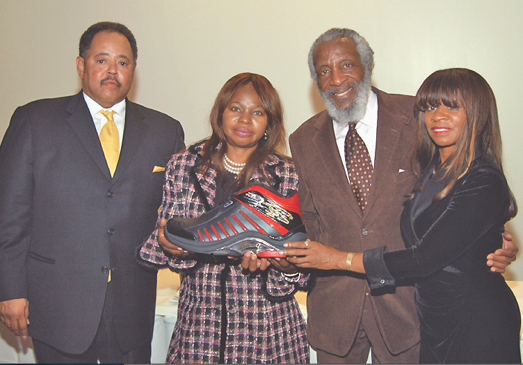 (From left) Lee Nelson, Dr. Laz, Dick Gregory and Dr. Jynona Norwood display a shoe donated by Shaquille O'Neal for Faith I AM Center's food and toy giveaway on Dec. 21.