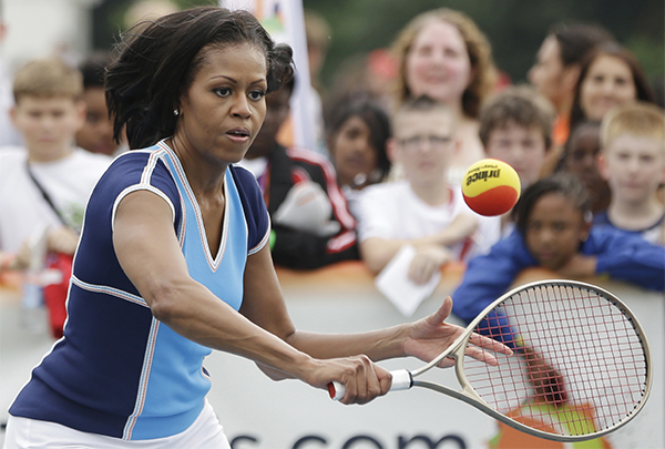 FILE - In this July 27, 2012, file photo, first lady Michelle Obama plays tennis with schoolchildren during a 'Let's Move!' event for about 1,000 American military children and American and British students at the U.S. ambassador's residence in London, ahead of the 2012 Summer Olympics. When Michelle Obama considered the daunting prospect of becoming first lady, she purposely avoided turning to books by her predecessors for guidance. Instead, she turned inward. (AP Photo/Lefteris Pitarakis, File)