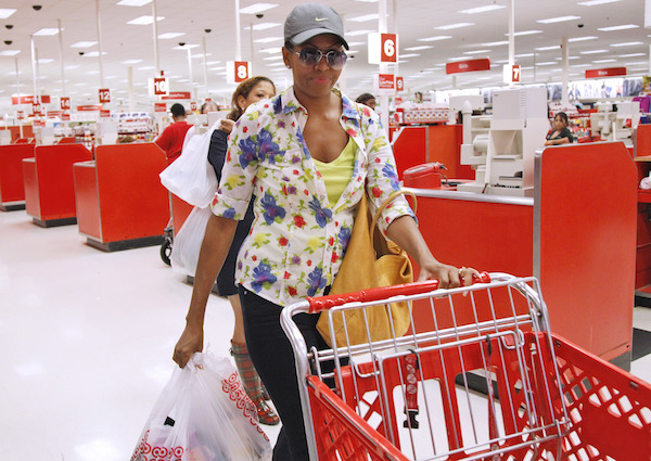 FILE - In this Sept. 29, 2011, file photo, first lady Michelle Obama, wearing a hat and sunglasses, stands in line at a Target department store in Alexandria, Va., after doing some shopping. When Michelle Obama considered the daunting prospect of becoming first lady, she purposely avoided turning to books by her predecessors for guidance. Instead, she turned inward (AP Photo/Charles Dharapak, File)