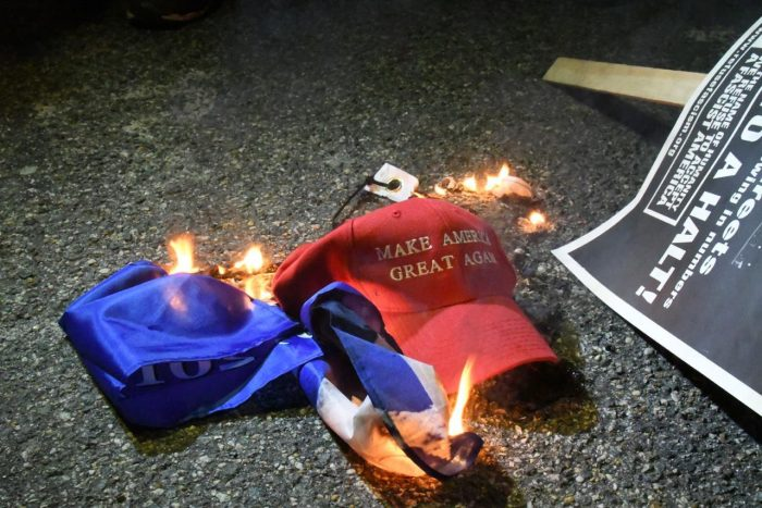 """A """"Make America Great Again"""" hat burns in the street in Washington, D.C. the night of the 2017 Inauguration. (Travis Riddick/The Washington Informer)"""